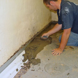 A contractor in Espanola installing a perimeter drain tile system during a sump pump installation.